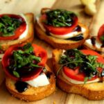 Bruschetta topped with fresh mozarella, tomates, basil and balsamic drizzle.