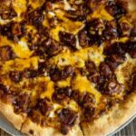 A hand-tossed pizza topped with BBQ sauce, fresh chicken and cheddar cheese.