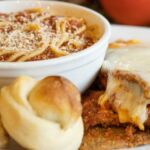 Eggplant parmesan with a side of pasta and two garlic rolls.