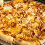A Hawaiian pizza topped with ham and chunks of pineapple.