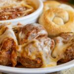 Meatballs covered with parmesan cheese with a side of pasta and sauce and two garlic rolls.