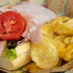 A classic ham and cheese sub with tomato, lettuce and black olives and a side of potato chips.