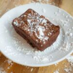 A freshly baked brownie on a white plate topped with powdered sugar.