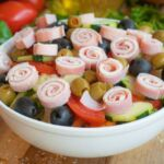 A chef's salad topped with olives, tomatoes, onions, cucumbers and rolled deli meat and cheese.