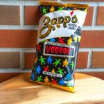A bag of Zappo Voodoo chips leaning against a brick wall.
