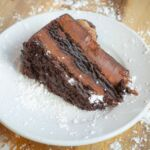 A slice of double chocolate cake on a white plate topped with powdered sugar.