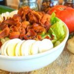 Cobb salad topped with bacon, hard boiled egg, tomatoes, cucumbers and walnuts.