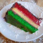 A slice of Italian rainbow cake on a white plate, topped with powdered sugar.