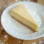 A slice of NY cheesecake on a white plate, topped with powdered sugar.